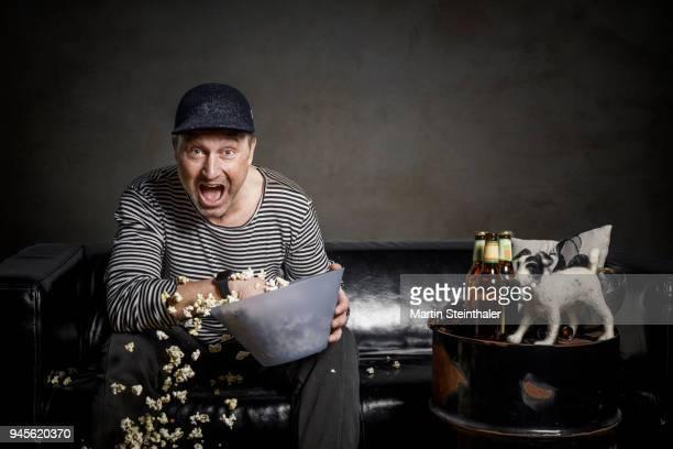 Mann mit Hund isst Popcorn auf Couch