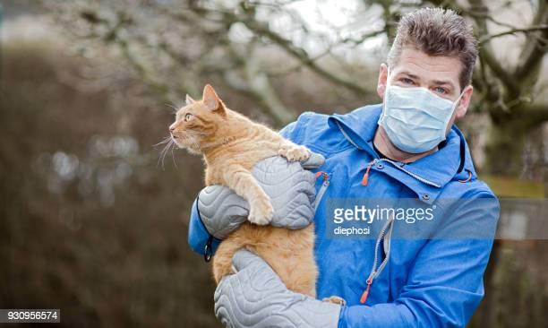 mann mit katzenallergie - flu mask stock photos and pictures