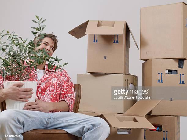 Mann mit Pflanze zwischen Umzugskartons