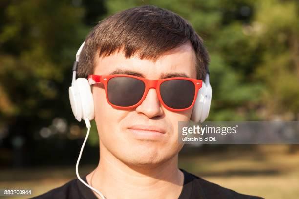 Mann mit weißen Kopfhörern und roter Sonnenbrille