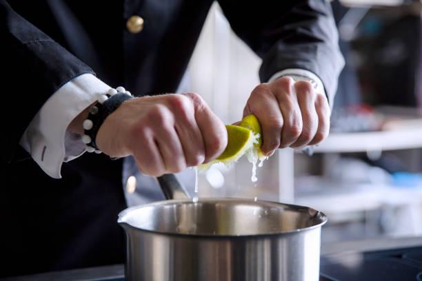 Mann presst frische Limetten mit der Hand aus - Limettensaft