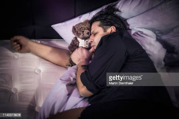 mann schläft mit teddybär und daumen im mund - chupando dedo - fotografias e filmes do acervo