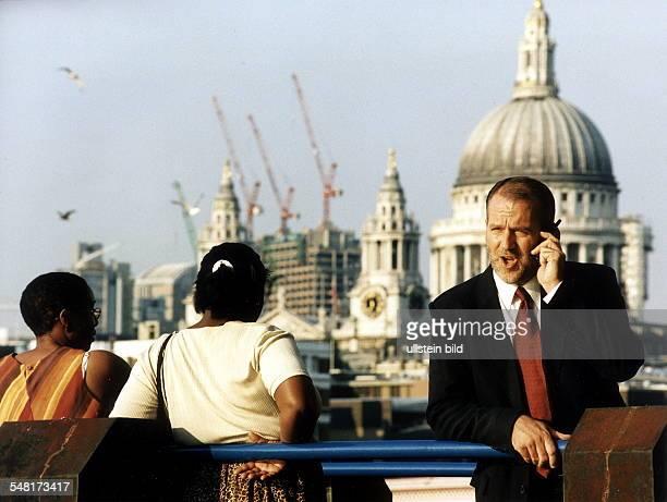 Mann telefoniert mit einem Mobiltelefon vor der Kulisse der St Pauls Cathedral in London 1999