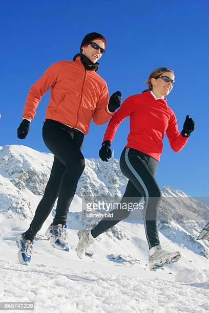 Mann und Frau joggen im Winter