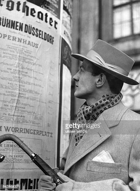 Mann vor einer Litfasssäule Er trägt einen LincolnHut ein Halstuch und einen Regenschirm1954Foto Schirner