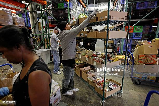 Manna Food Center Distribution Supervisor Alex Ramirez and a team of volunteers sort donated food into individual boxes at the center November 17...