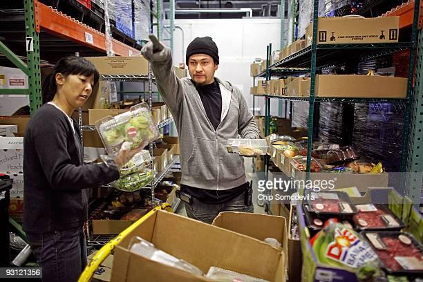 Manna Food Center Distribution Supervisor Alex Ramirez and volunteer Sharon Hwang sort donated food into individual boxes at the center November 17...
