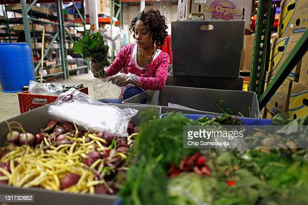 Manna Food Center volunteer Ronia Johnson of Germantown Maryland sorts and packages fresh vegetables to be given to more than 150 people who came to...