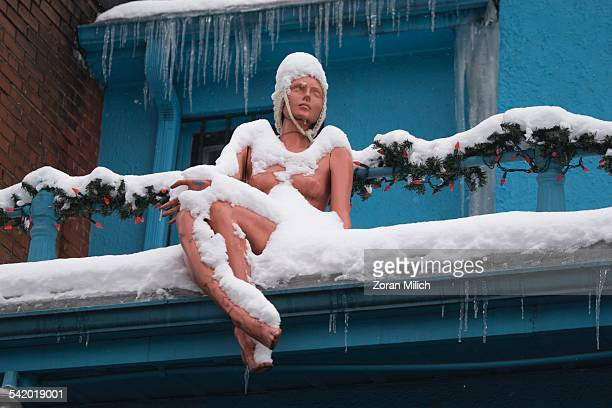 Mannequin covered in snow on top of a vintage clothing store during cold weather in Toronto Ontario Canada Display only not a trade mark