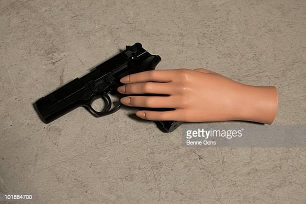 A mannequin hand and a handgun