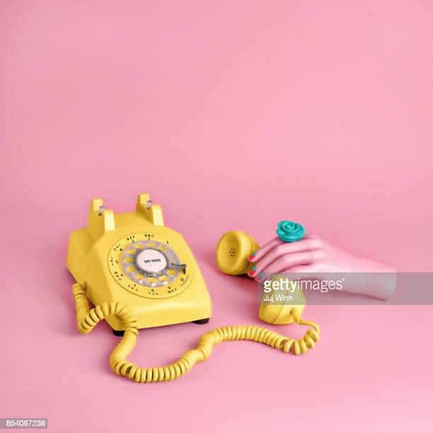 mannequin hand holding yellow rotary phone - kitsch stock pictures, royalty-free photos & images