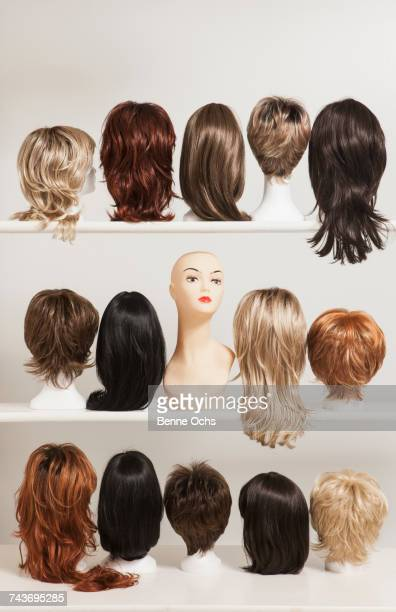 Mannequin head amidst various wigs on shelves against white background