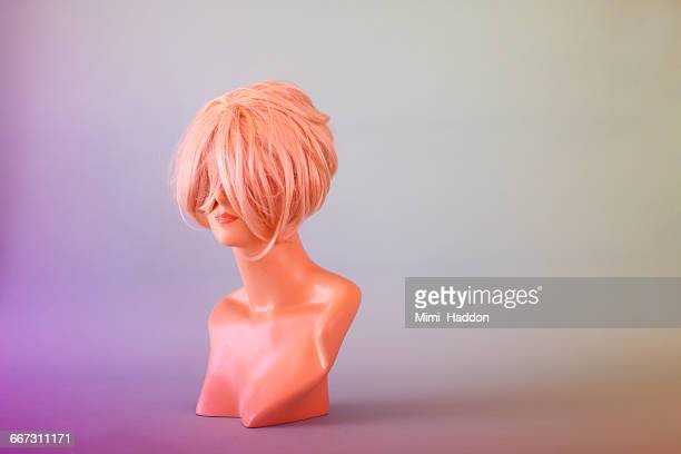 mannequin head hiding behind blonde wig - wig stock pictures, royalty-free photos & images