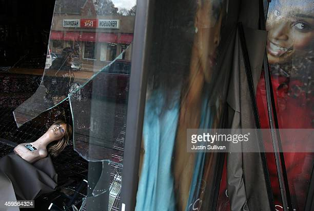 A mannequin head sits behind broken glass at a beauty supply business that was damaged during a demonstration on November 25 2014 in Ferguson...