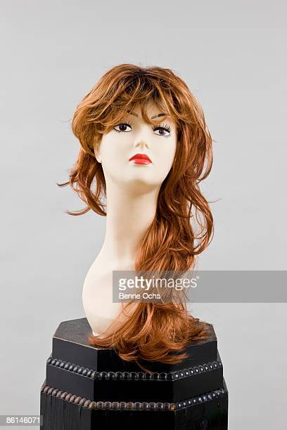 A mannequin head wearing a wig on a pedestal
