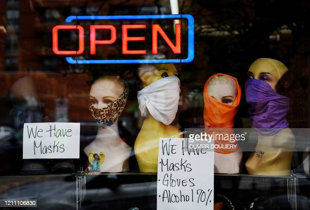 Mannequin heads wear masks in the window of a small boutique advertising availability of masks gloves and other pandemic necessities amid the...