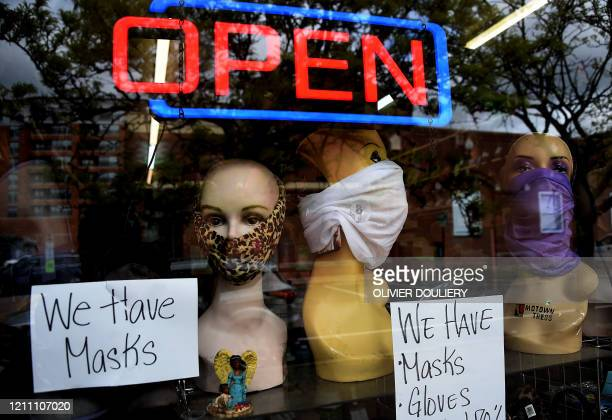 Mannequin heads wear masks in the window of a small boutique advertising availability of masks, gloves, and other pandemic necessities amid the...
