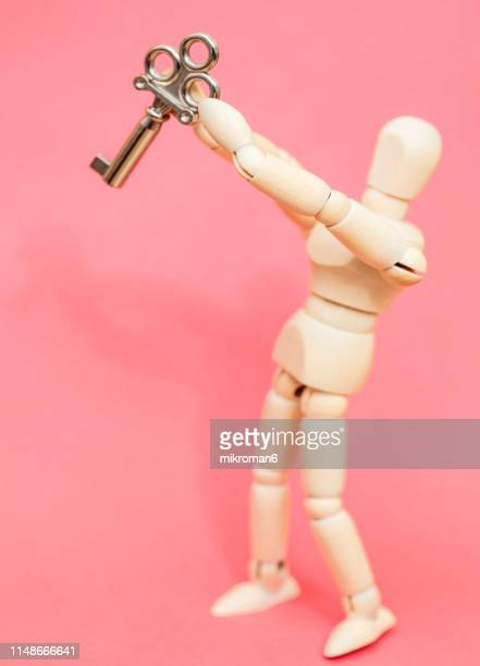 mannequin holding a small key - security code stock photos and pictures