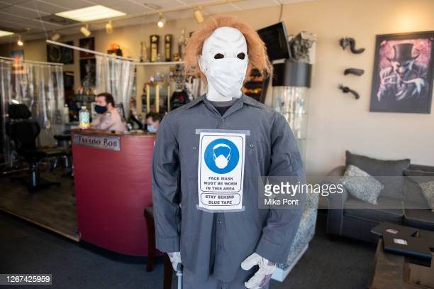 Mannequin in a costume mask is seen with a sign requiring the wearing of face masks at Skin Deep Tattoo as the city continues Phase 4 of re-opening...