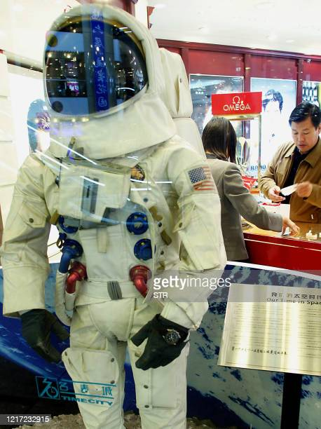Mannequin in a space-suit at a window display of a watch shop in a departmental store in Beijing 12 October 2003. Thousands of amateur satellite...