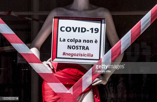 A mannequin in the window of a clothing store has a notice which reads Covid is not our fault attached as the owners protest it's mandatory closure...