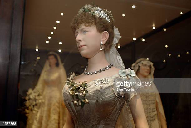 Mannequin of Britain's Queen Mary, wearing her wedding dress, stands in front of models of Queen Elizabeth and the Queen Mother April 30, 2002 at the...