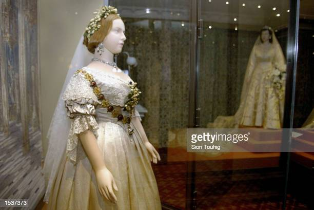 A mannequin of Britain's Queen Victoria wearing her wedding dress stands in front of a model of Queen Elizabeth April 30 2002 at the launch of the...