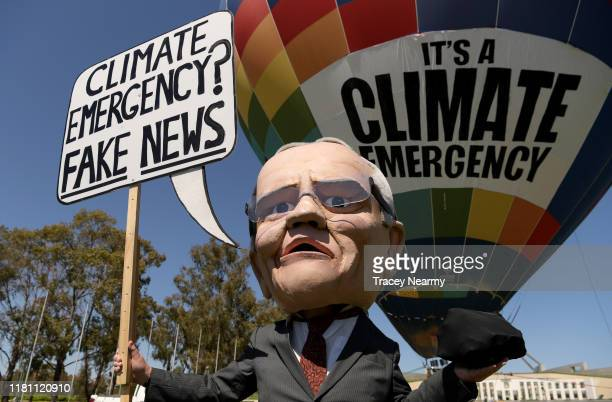 A mannequin of Prime Minister Scott Morrison holding a lump of coal with hot air ballon with 'Climate Emergency' on it during a protest in front of...
