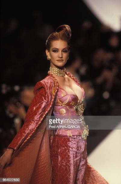 Mannequin portant un manteau et un pantalon de velours matelassé et un bustier rose au défilé Dior Haute Couture Printemps/Eté en janvier 1995 à...