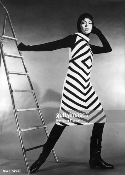 Mannequin portant un modèle Castillo Tricots une robe blanche striée de larges raies géométriques noires formant un losange sur le buste en France le...