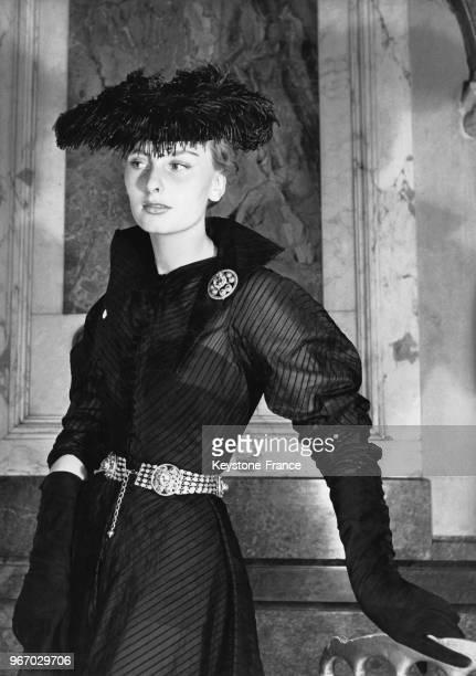 une robe en organdi noir rayé avec une ceinture copiée sur un bijou ancien et un chapeau garni de plumes d'autruche noires à Paris France le 25 mai...