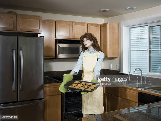 Mannequin portraying a woman holding a tray of biscuits