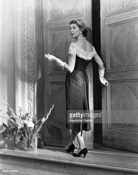 Mannequin présentant un modèle Ceil Chapman de la Collection Printemps 1956 une robe d'aprèsmidi en organza noir réhaussée de fleurs blanches brodées...