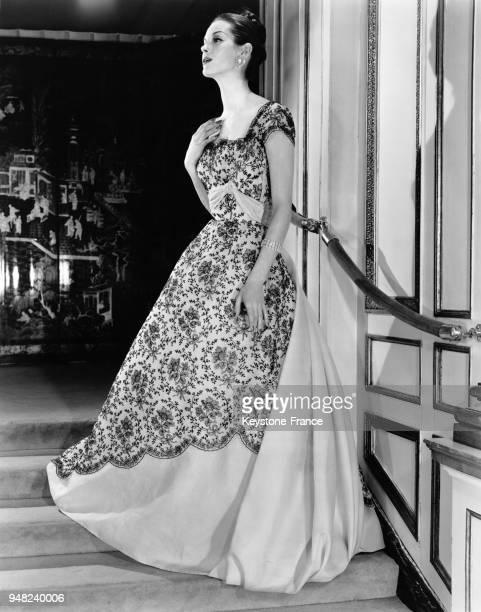 Mannequin présentant un modèle Hattie Carnegie de la Collection Printemps 1956 une robe de bal en organza rose pâle brodée de noir avec des bijoux...
