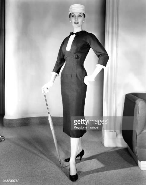 Mannequin présentant un modèle Herbert Sondheim de la Collection Printemps 1956 une robe en lin bleu marine avec un corsage plissé et des manches en...