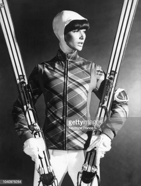 Mannequin présentant un modèle pour les sports d'hiver une casaque en tissu à large écossais rouge vert et jaune avec une patte unie sur les côtés...