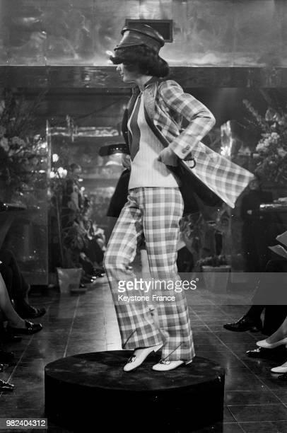 Mannequin présentant un modèle Ted Lapidus un ensemble veste et pantalon à carreaux avec casquette en France le 4 mars 1969