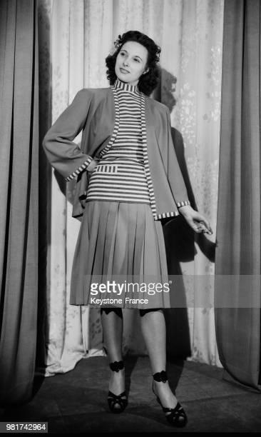 Mannequin présentant un tailleur de lainage composé d'une jupe plissée et d'une veste longue en 1947