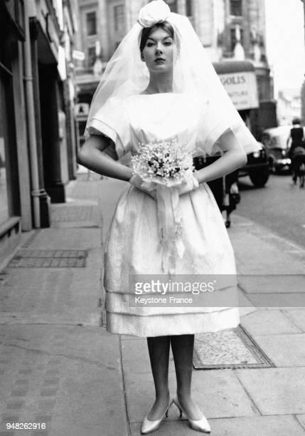 Mannequin présentant une robe de mariée courte en moire blanche à Londres RoyaumeUni le 12 mai 1959