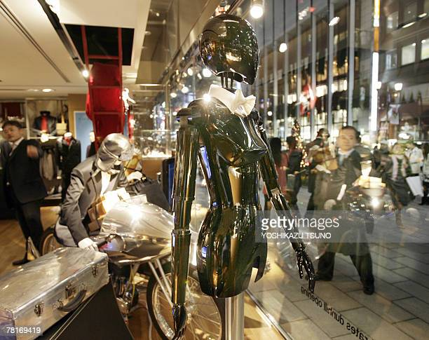 A mannequin robot named Palette moves its arms and head to strike a pose like a model to attract shoppers in a show window of British men's fashion...