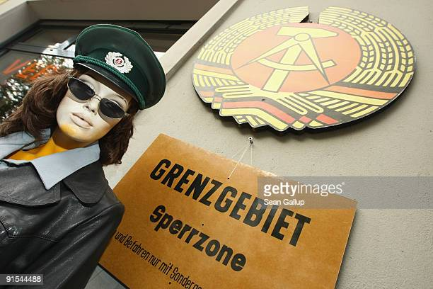 A mannequin sporting an East German army soldier's hat stands next to a sign that reads Border Area Prohibited Zone and the state seal of the former...