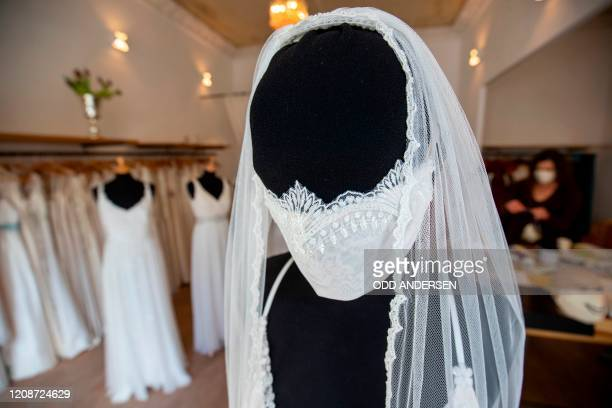Mannequin wearing a wedding dress with matching protective mask is seen as wedding dress and evening wear designer Friederike Jorzig speaks with a...