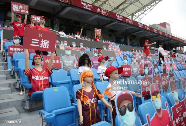 Mannequins and fake masked audience placards are placed at the Taoyuan Baseball stadium before the opening match for the Chinese Professional...