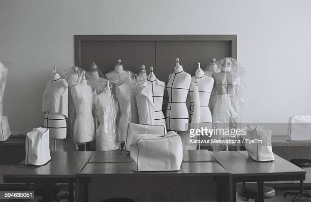 mannequins and table against wall in room - dressmaker's model stock photos and pictures