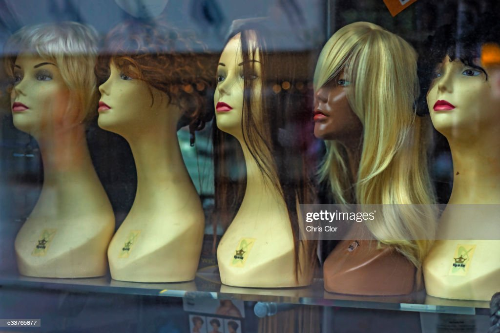 Mannequins and wigs in store window : Foto stock