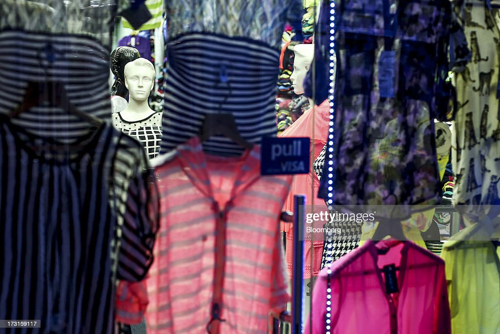 Mannequins are seen through gaps between clothing displayed for sale in the window of a garment store in the suburb of Bandra in Mumbai, India, on Saturday, July 6, 2013. India's consumer price index (CPI) figures for June are scheduled to be released on July 12. Photographer: Dhiraj Singh/Bloomberg via Getty Images