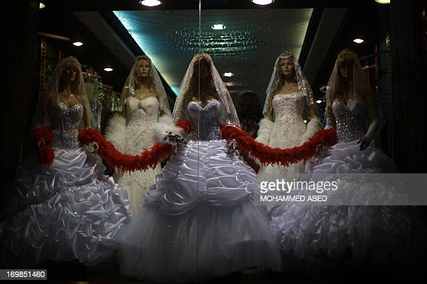 Mannequins display wedding gowns designed by the alAshi family at their atelier in Gaza City on June 3 2013 The family started their own clothing...