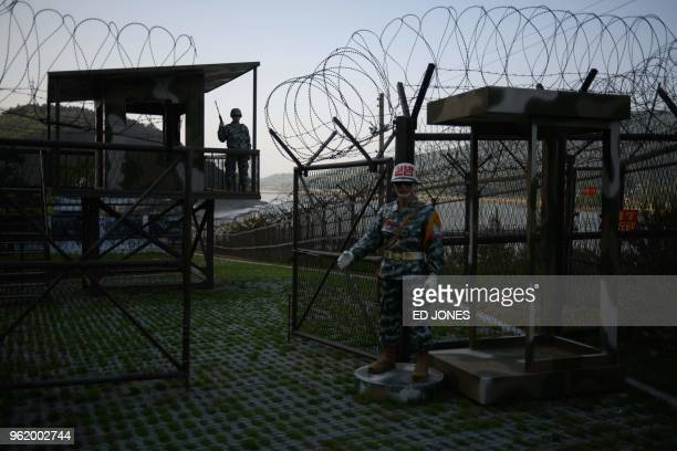 TOPSHOT Mannequins of South Korean soldiers stand before a guard post open to visitors beside the barbed wire fence of the Demilitarized Zone between...