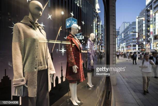 Mannequins stand in a window display of a store at night in the Ginza area of Tokyo Japan on Tuesday Aug 21 2018 Japan is scheduled to release...