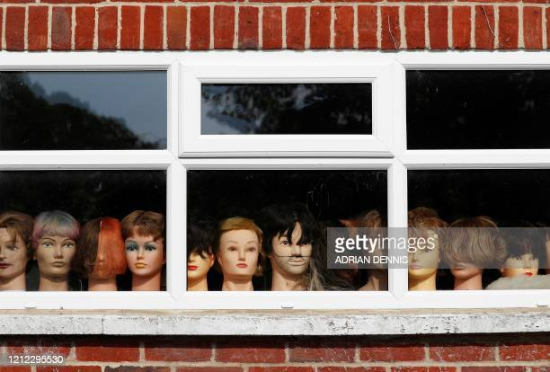 Mannequins with wigs are pictured looking out of the window of a hairdresser's salon closeddown due to COVID19 in Goring west of London on May 9 as...